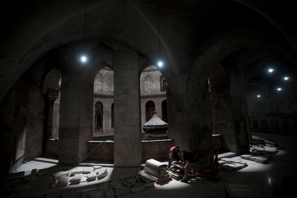 Членове на екипа по консервация повдигат плоча, за да я почистят и сканират дигитално, преди да я монтират обратно във фасадата на Едикула – храмът, в който се помещава това, което се счита, че е гробницата на Иисус. Credit: Oded Balilty, AP for National Geographic