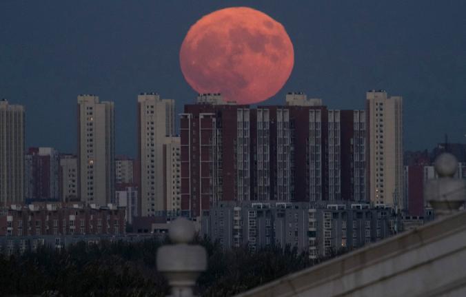 Луната изгрява над жилищна сграда в Пекин. Credit: Ng Han Guan, Associated Press