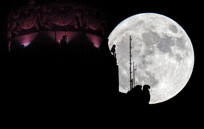 Супер луната изгрява зад скулптура на орел на върха на LeVeque Tower в Кълъмбъс, щата Охайо в неделя. Credit: Adam Cairns, The Columbus Dispatch, Associated Press