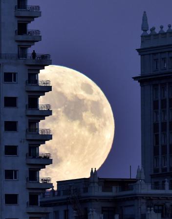 Мъж се любува на Супер Луната от терасата си в Мадрид. Credit: Gerard Julien, Afp, Getty Images