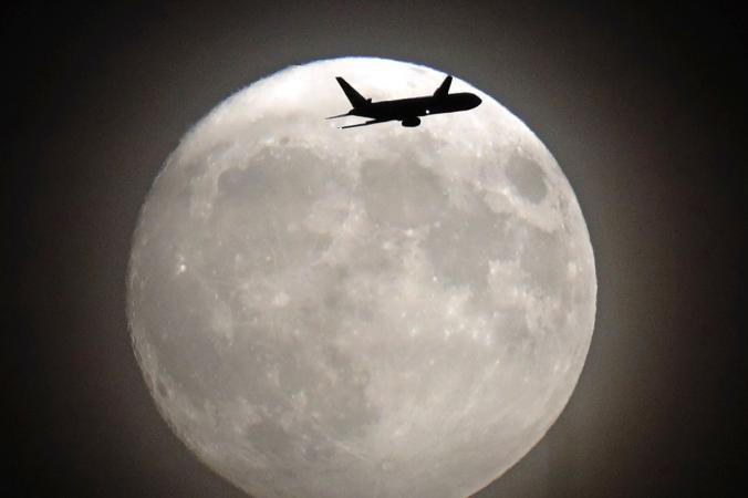 """Самолет прелита пред Супер Луната на път за летище """"Хийтроу"""" в Лондон. Credit: Adrian Dennis, Afp, Getty Images"""