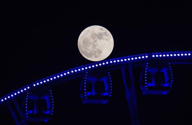 Голямата ярка луна е надвиснала над виенското колело в Хонг Конг. Credit: Anthony Wallace, Afp, Getty Images