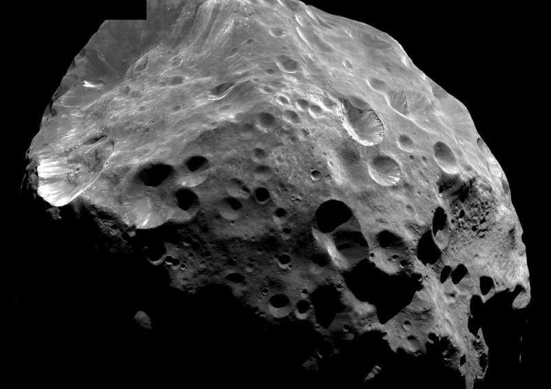 Наподобяващият пемза вид на Феба и обратното ѝ въртене могат да бъдат обяснени единствено с това, че произходът ѝ е отвъд Слънчевата система – там, където са разположени газовите гиганти. Credit: NASA/JPL/Space Science Institute.