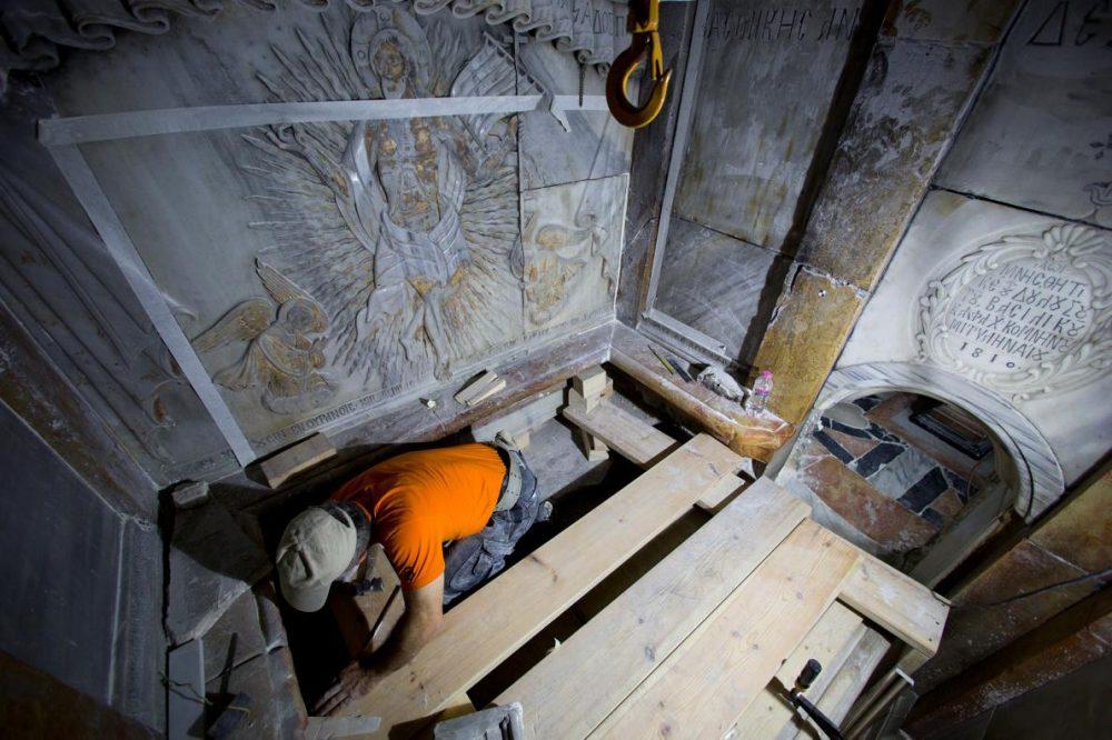 Реставратор почиства повърхността на каменната плоча на гроба.
