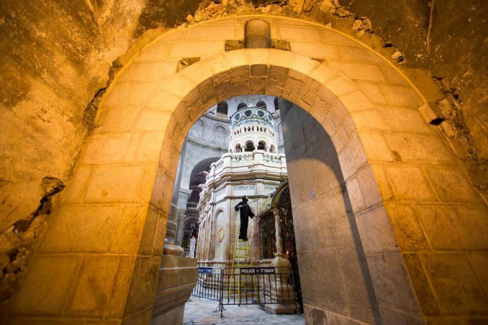 Коптски монах бърше праха на входа на параклис на гърба на едикулата.