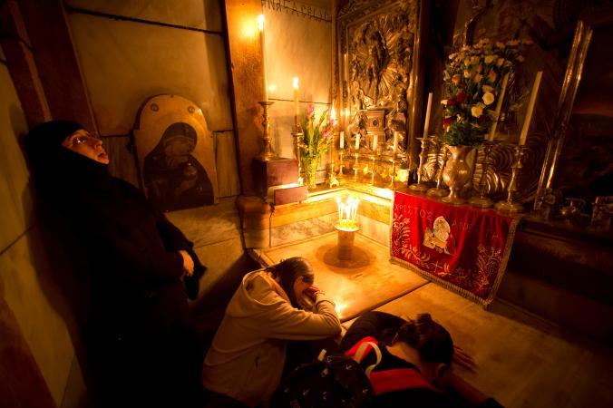 Жени се молят върху мраморния капак на гробницата преди той да бъде отстранен за възстановителни работи. Credit: Oded Balilty, AP for National Geographic