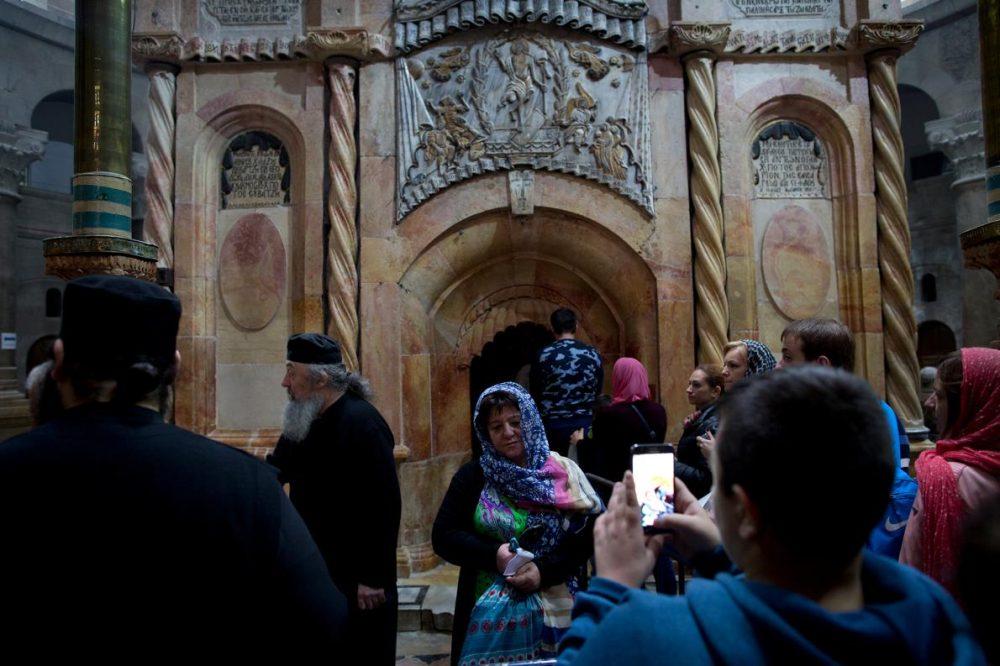 Жена позира пред едикулата, в която се помещава гробът на Иисус.