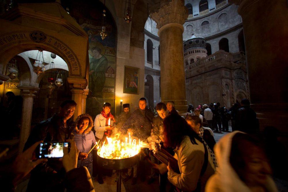 Хората палят свещи на входа на ротондата в Църквата на Божи гроб.