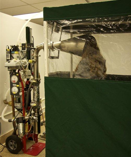Участник в проучване стои в The Gesundheit II machine (машина на здравето II), която служи да улавя и анализира вируса в издишания въздух във Факултета по обществено здраве към университета в Мериленд. Credit: University of Maryland